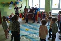 2-Dzieci-rzucaja-biale-i-niebieskie-nakretki-na-rozlozony-na-podlodze-material