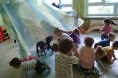 3-Dzieci-chowaja-sie-pod-materialem-trzymanym-przez-nauczycielke-rytmiki