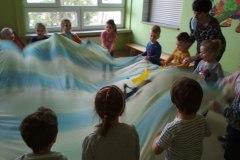 4-dzieci-ustawione-w-kole-wachluja-bialo-niebieskim-materialem