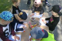 2-Dzieci-w-ogrodzie-stoja-przy-stolikach-i-rysuja