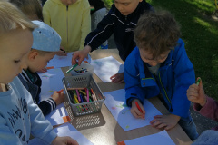 3-Dzieci-stoja-przy-stolikach-i-rysuja-kredkami