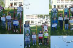 4-Dzieci-stoja-przy-drabinkach-w-ogrodzie-przedszkolnym-i-prezentuja-wykonane-rysunki